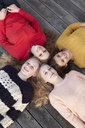 Portrait of four teenage girls head to head on patio - CUF33789