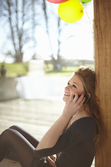 Teenage girl talking on mobile at birthday party - CUF33804