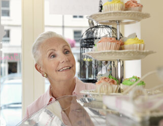 Senior woman looking at cupcakes in cafe - CUF33813