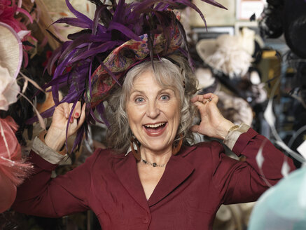 Glamorous senior woman trying on hat - CUF33816
