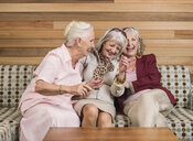 Senior women friends laughing on sofa - CUF33819