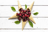 Arrangement of five ice cream cones and pile of cherries on white wood - SARF03795