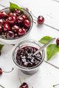 Jar of cherry jam and cherries on white wood - SARF03801