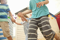 Cropped shot of brothers and toddler sister running, Southwold, Suffolk, UK - CUF33928
