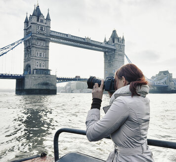 Female photographer taking photograph of Tower Bridge London, UK - CUF33937