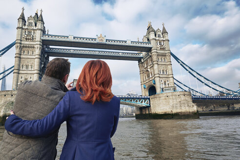 Mature tourist couple photographing Tower Bridge, London, UK - CUF33940
