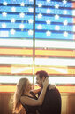 Romantic young couple and neon american flag, New York City, USA - CUF33955