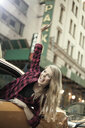 Young woman waving out from yellow cab, New York City, USA - CUF33958