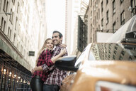 Young couple hugging next to yellow cab, New York City, USA - CUF33961