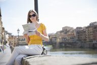 Woman on riverside in Florence, Italy looking at map - CUF33979