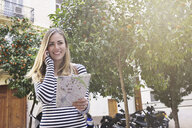 Young female tourist with map and cellphone, Valencia, Spain - CUF33997