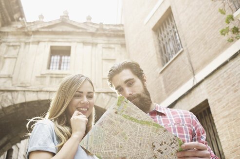Young tourist couple looking at map outside Valencia Cathedral, Valencia, Spain - CUF34012