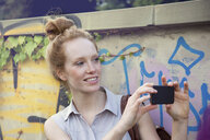 Young woman taking photograph on smartphone - CUF34027
