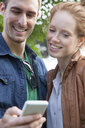 Young couple looking at smartphone - CUF34054