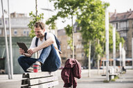 Man with takeaway coffee sitting on bench using tablet - UUF14281