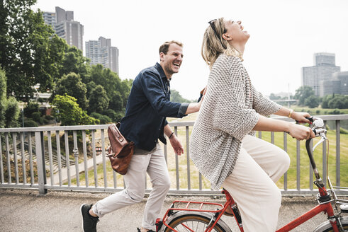 Happy couple crossing a bridge with bicycle and by foot - UUF14302