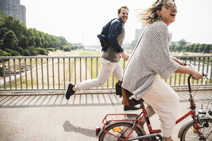 Happy couple crossing a bridge with bicycle and by foot - UUF14305