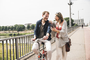 Happy couple with bicycle and cell phone crossing a bridge - UUF14308
