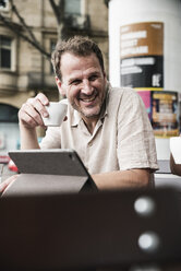 Smiling man with tablet and coffee at an outdoor cafe - UUF14311