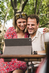 Smiling couple sharing tablet at an outdoor cafe - UUF14314