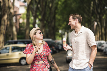 Happy couple with ice cream cones walking in the city - UUF14317