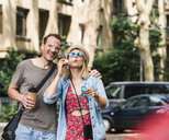 Happy couple with coffee to go blowing soap bubbles in the city - UUF14320