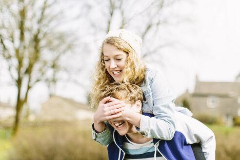 Teenage girl on piggyback covering teenage boys eyes - CUF34142