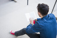 Young man sitting on steps reading book - CUF34163