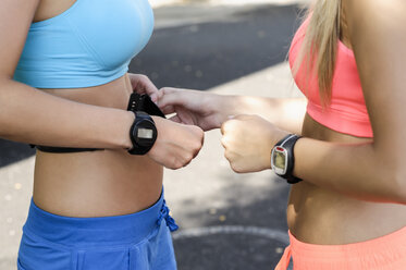 Young female athletes checking heart rate monitors - CUF34193