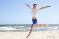 Young man leaping mid air on beach, Port Melbourne, Melbourne, Australia - CUF34220