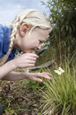 Close up of schoolgirl looking at butterfly in garden - CUF34274