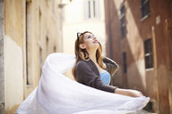 Young woman swirling her scarf on street, Rome, Italy - CUF34316