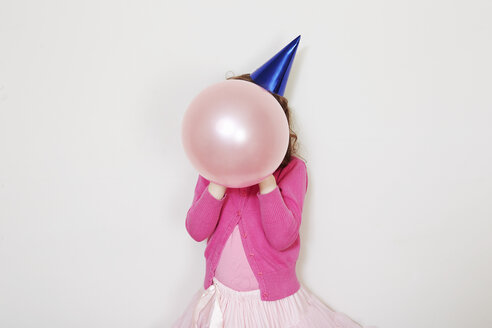 Girl holding pink balloon in front of face - CUF34391
