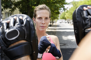 Female boxer and personal trainer in park - CUF34421