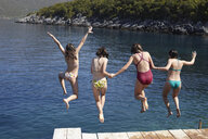 Four girls jumping from pier into the sea - CUF34424
