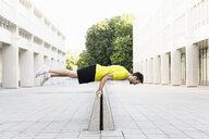 Young man balancing horizontally on divider - CUF34430