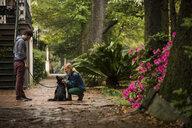 Couple with dog behind house, Savannah, Georgia, USA - ISF14295