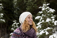 Portrait of laughing young woman in front of snow covered fir trees - ISF14307