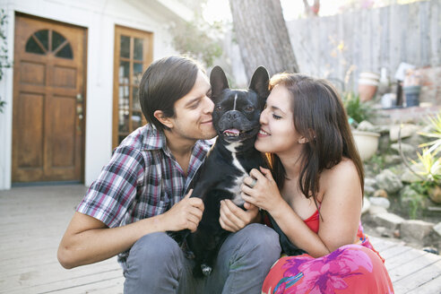 Young couple sitting on patio snuggling up to dog - ISF14349