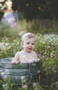 Portrait of baby girl bathing in a tin bathtub in a wild flower meadow - ISF14367