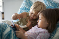 Girl and toddler sister sitting up in bed using digital tablet - ISF14373