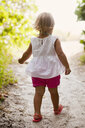 Rear view of female toddler toddling on woodland beach path, Anna Maria Island, Florida, USA - ISF14385