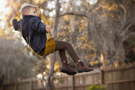 Young boy swinging high on garden swing - ISF14403