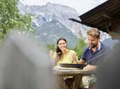 Happy couple having a snack at a hut in the mountains - CVF00856