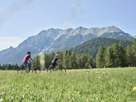 Austria, Tyrol, Mieming, couple riding bike in alpine scenery - CVF00859