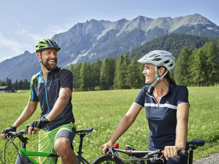Austria, Tyrol, Mieming, happy couple with mountain bikes in alpine scenery - CVF00865