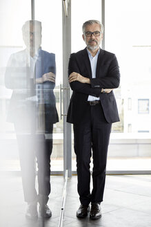 Portrait of confident businessman standing in office - RBF06314