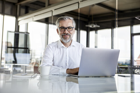 Portrait of confident businessman with laptop at desk in office - RBF06317