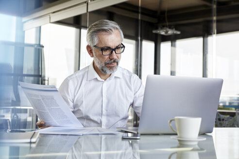Businessman working at desk in office - RBF06323
