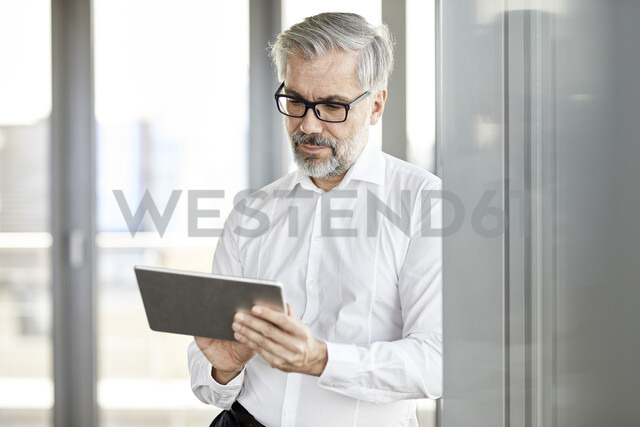 Businessman standing at the window using tablet - RBF06338 - Rainer Berg/Westend61